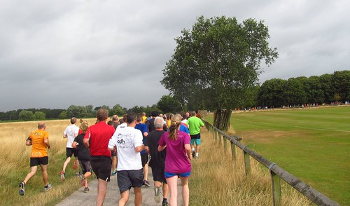 Runners going past the cricket field at 1k