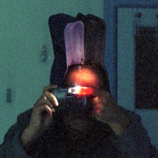 reflected self-portrait with Hanimex Genie Motor camera and bifid hat