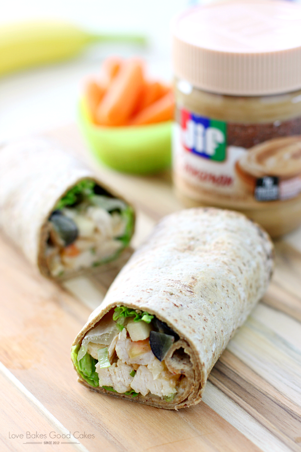PB Apple Chicken Salad Wraps on a cutting board with a jar of Jif peanut butter.
