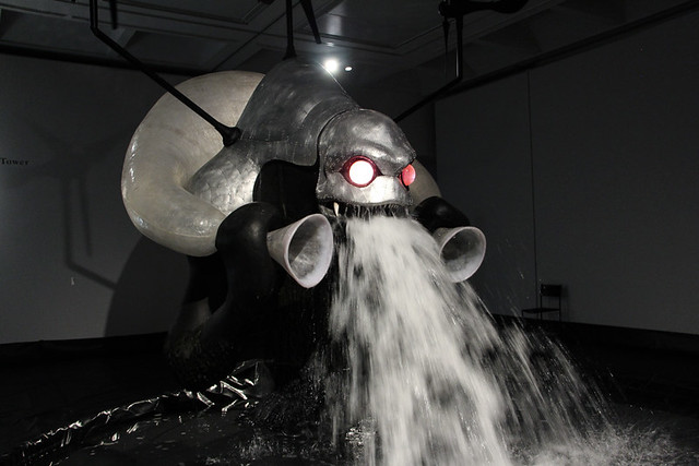 《風神の塔》 福島県飯舘村の電力会社のモニュメントを想定して制作。阿武隈大地をリサーチし、鍾乳洞や現地の妖怪の民間伝承などからヒントを得た造形にしている。風力発電機を備え、水を汲み上げ、噴き出すことを繰り返す。「パンテオン-神々の饗宴-」展で風神として発表された。
