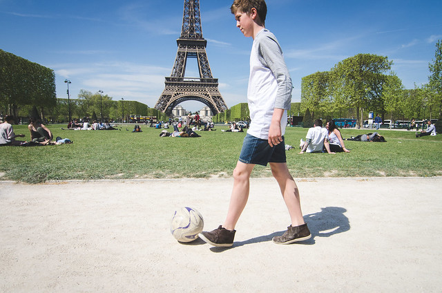 A young buy dribbles a soccer ball past the Eiffel Tower in Paris, France.