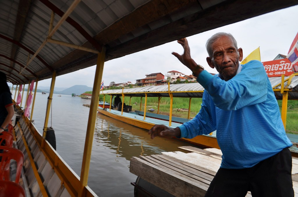 Captain of the longtail boat pushes off before setting sail up the Mekong River in Chiang Khan, Thailand, March 2015.