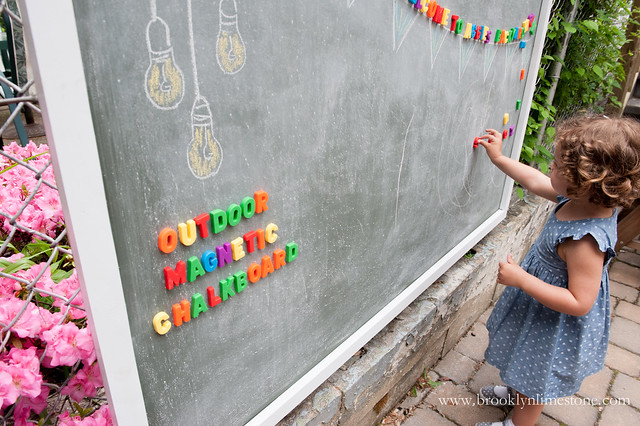 Aggie playing with magnet letters on her DIY Outdoor Magnetic Chalkboard | Brooklyn Limestone