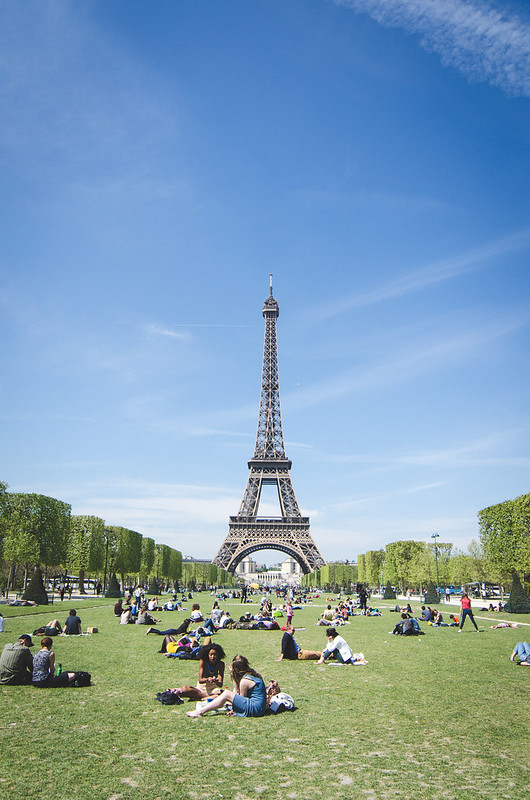 A sunny day at the Eiffel Tower, crowds of visitors picnic on the green lawn of the monument.