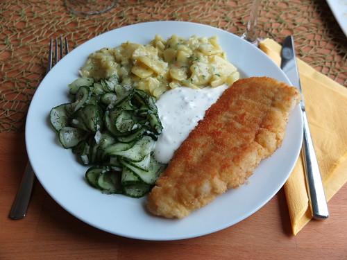 Paniertes Kabeljaufilet mit Joghurtsoße, Kartoffelsalat und Gurkensalat