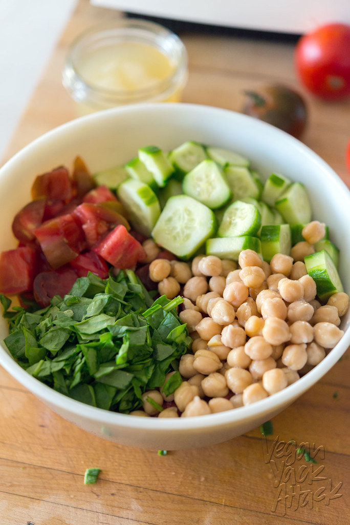 Mixing bowl with chickpeas, spinach, tomato, and cucumber on a cutting board