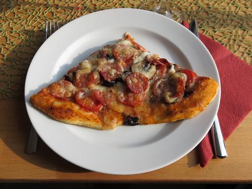 Pizza mit Tomaten, Mozzarella, Oliven, Champignons und Paprikasalami