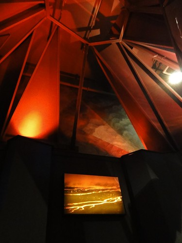 Image shows the inside of the Cascades volcano display. It's a dark, conical room whose ceiling is made up of wide slabs of metal tipped toward each other, with open spaces between them. They're lit by a few red-orange lights. On the wall is an illuminated photo of a lava flow at night.