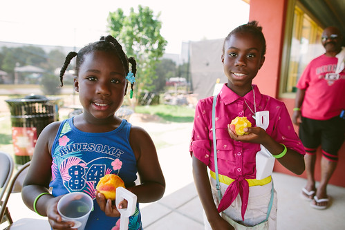 Two girls enjoying local peaches at a Summer Meals Site
