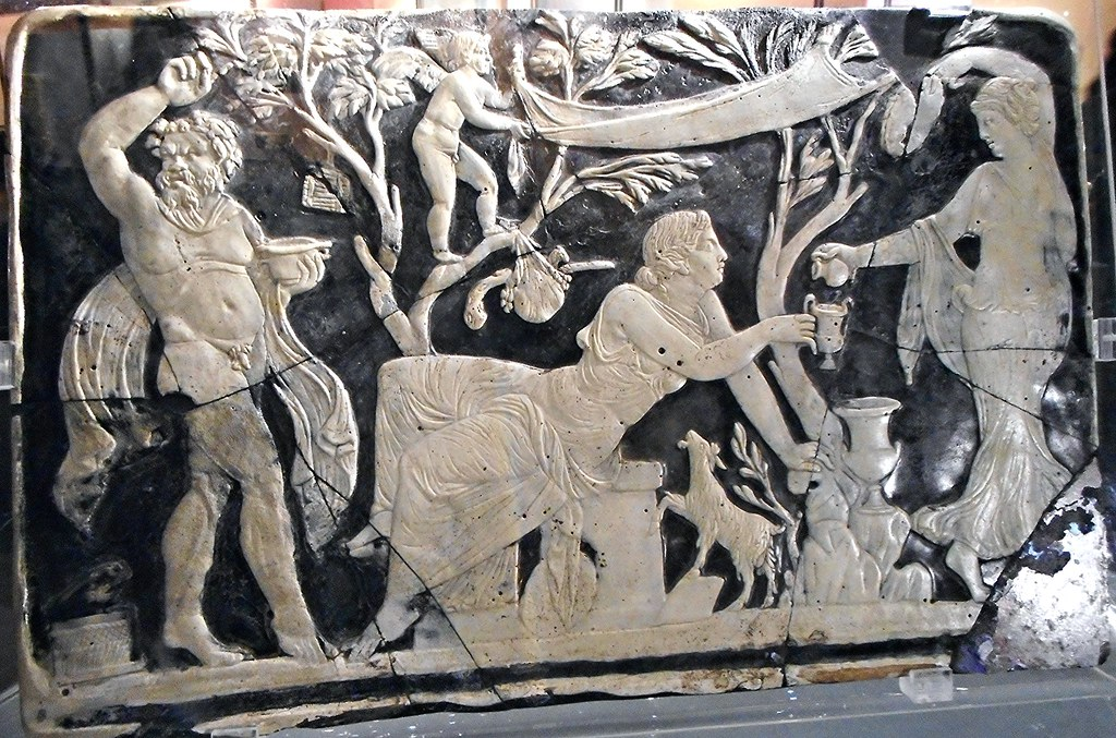 """Panel with Maenad pouring wine for Ariadne in the presence of a Satyr dancing between trees from which hang objects of the cult of Dionysos - glass cameo (1st century AD) from Pompeii - Exhibition """"Myth and Nature"""" at Archaeological Museum of Naples, unti"""