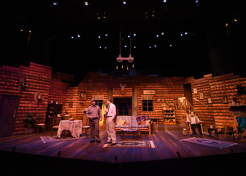 """A fishing lodge scene is set for the play """"The Foreigner,"""" with three actors on stage."""