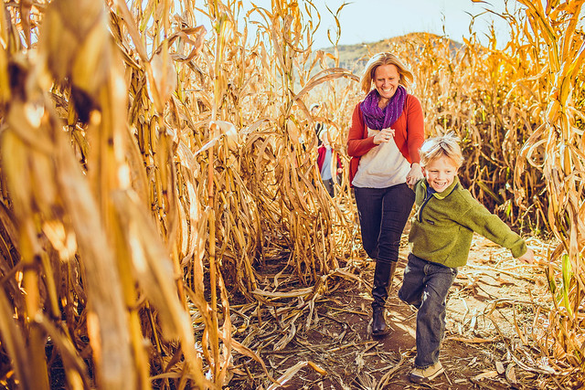 A mother and son run happily through a corn maze at a farm in Roanoke