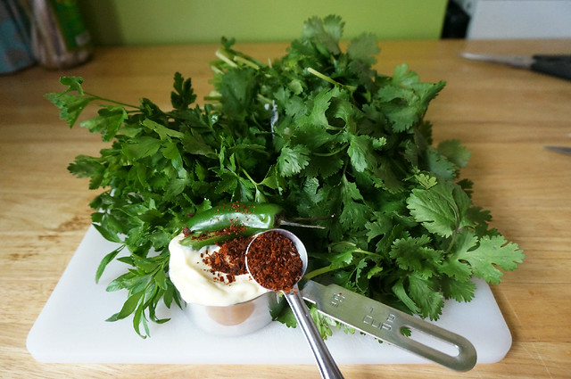 A cup of mayonnaise, topped with a serrano chile, is nestled in a bed of herbs, with a teaspoon of red pepper spilling out on top; it's either sauce ingredients or a crazy salad