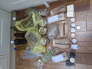 Ikaria produce on my kitchen floor. Wine, honey, olive oil, mountain tea, herbs, soaps, cosmetics. About half of it unlabeled, given to me as presents.