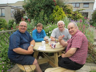 Phil, Jo, Andy, Geoff sit around garden table enjoying strawberries and coffee