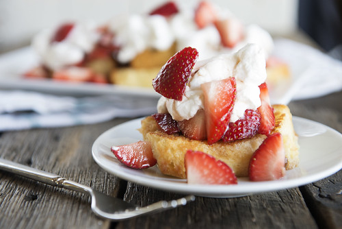 toasted pound cake with strawberries and whipped cream on a plate with a fork on a wood table