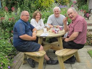 Phil, Sue, Andy, Geoff sit around garden table enjoying strawberries and coffee