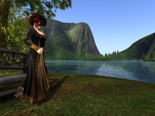 Image Description: Woman wearing a black dress with gold symbols on it wearing a black hat with a veil. She is standing to the left in front of a view of a lake flanked by mountains.