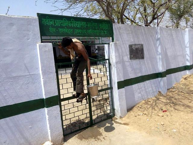 स्कूल में हैण्डपम्प से इस तरह से पानी भरते हैं लोग