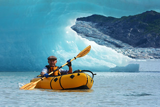 Packrafting past an iceberg arch in a Kokopelli Renegade packraft. Spencer Glacier, Alaska | by Paxson Woelber