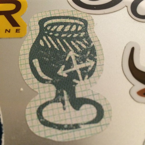 A very close up shot of a sticker; it's a stylized tuilp glass with the Crux Brewing logo on it.
