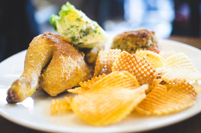 A main course Juicy roast chicken is complemented by crispy chips at Cafe Constant in Paris, France.