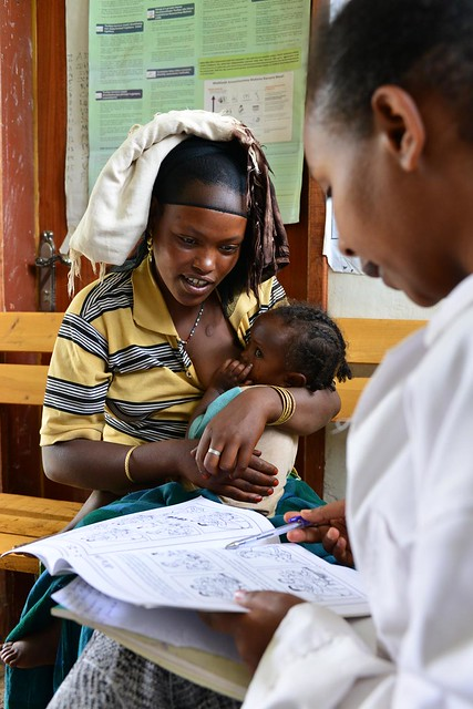 Health extension worker Elsebeth Aklilu refers to a family health card while counseling Kedo Abdula, who is holding her 21-month-old daughter, Fenete Abdela, on best nutrition practices, at the health post in the village of Maderia, in Gemechis, a woreda (district) of Oromia Region.
