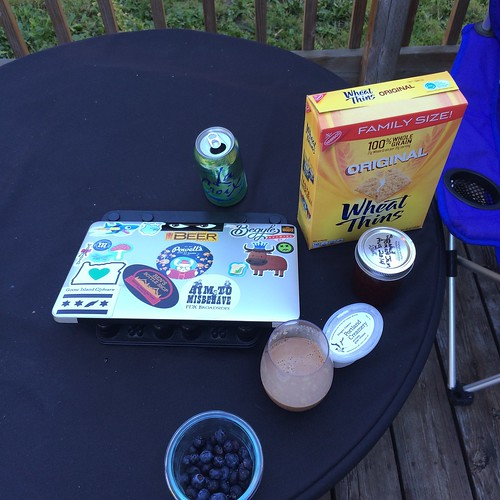 A closed laptop , covered in stickers, on a table next to a chocolate milk, some berries, some jam, and some wheat thins crackers.