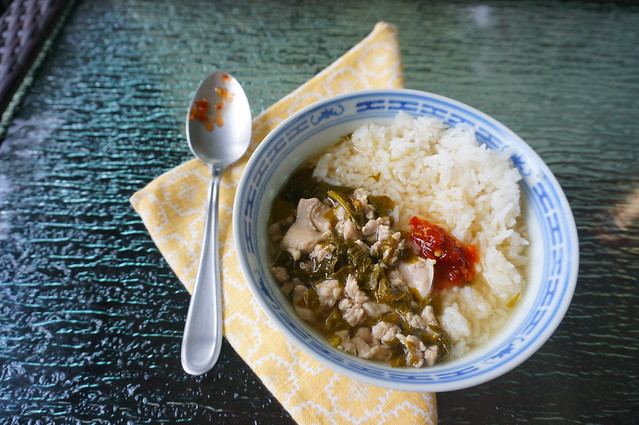 Simple sorrel soup with a dollop of bright red chili paste, all in a blue-patterned porcelain bowl with some rice