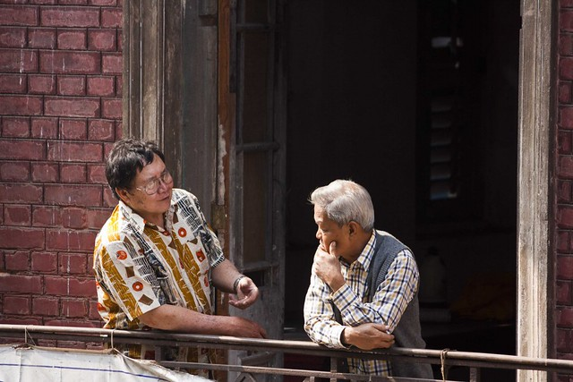 Chinese Olderly People in Tong On Church balcony in Tiretta Bazar, Kolkata, India