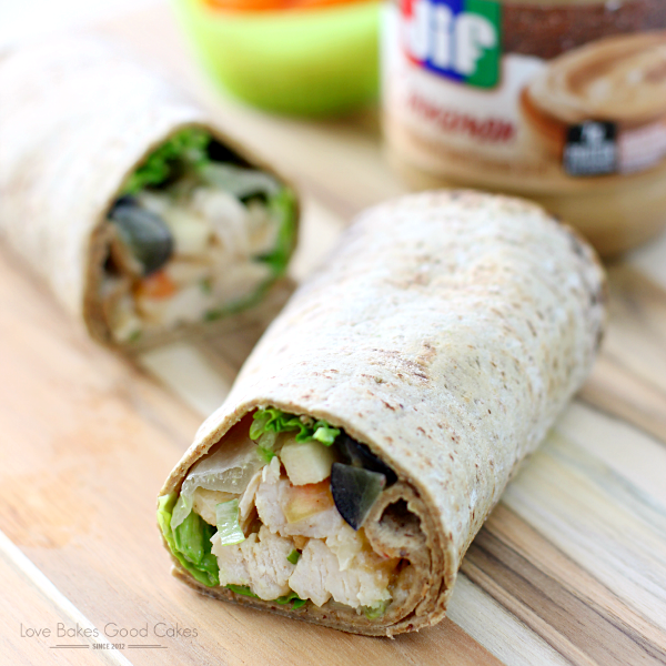 PB Apple Chicken Salad Wraps on a cutting board with a jar of Jif peanut butter close up.