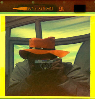 reflected self-portrait with Contaflex 126 camera and orange hat