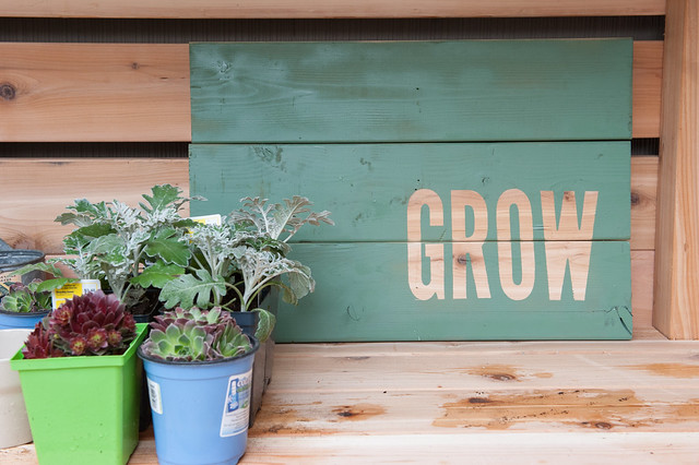 close up of GROW sign make from 3 pieces of wood painted green with a the word GROW showing through in the natural wood tone