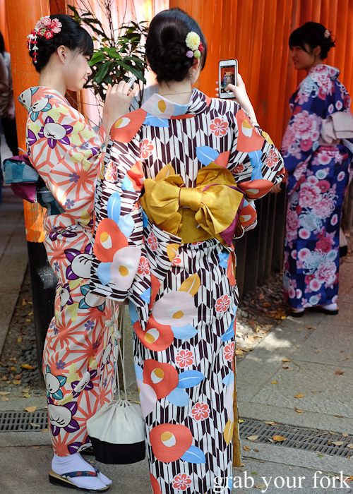 Locals in kimonos taking photos at Fushimi Inari Shrine, Kyoto, Japan