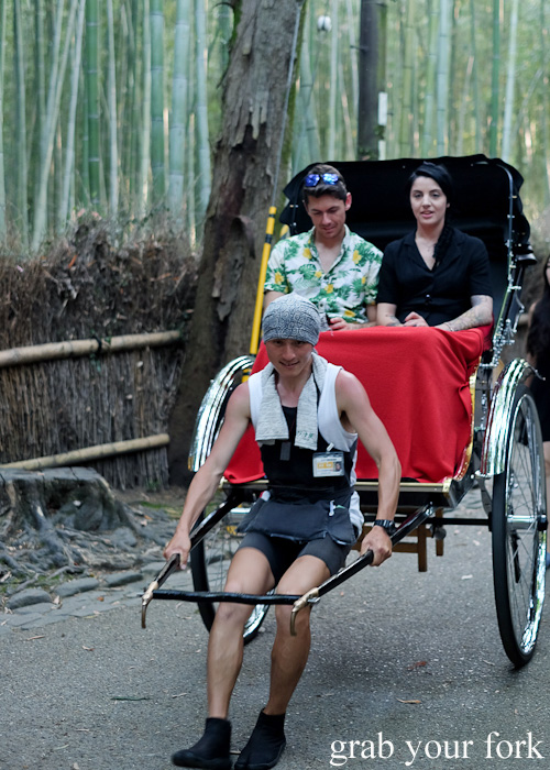 Tourists on a jinrikisha Japanese rickshaw at Arashiyama Bamboo Grove, Kyoto, Japan