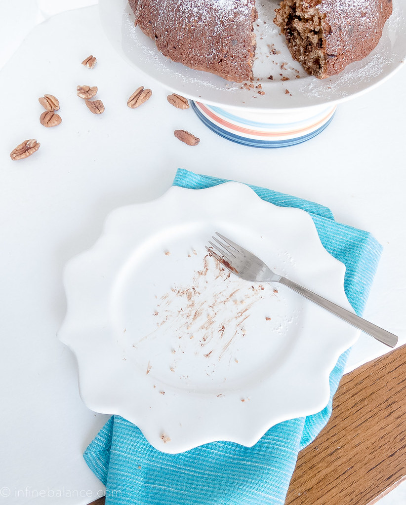 an empty white plate with chocolate and a pecan chocolate chip cake in background