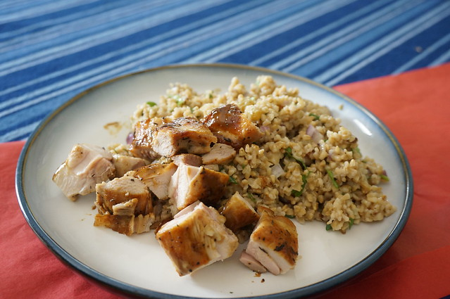 Pan-seared lemony chicken thighs, chopped up, scattered over and near a bed of steel-cut oat salad