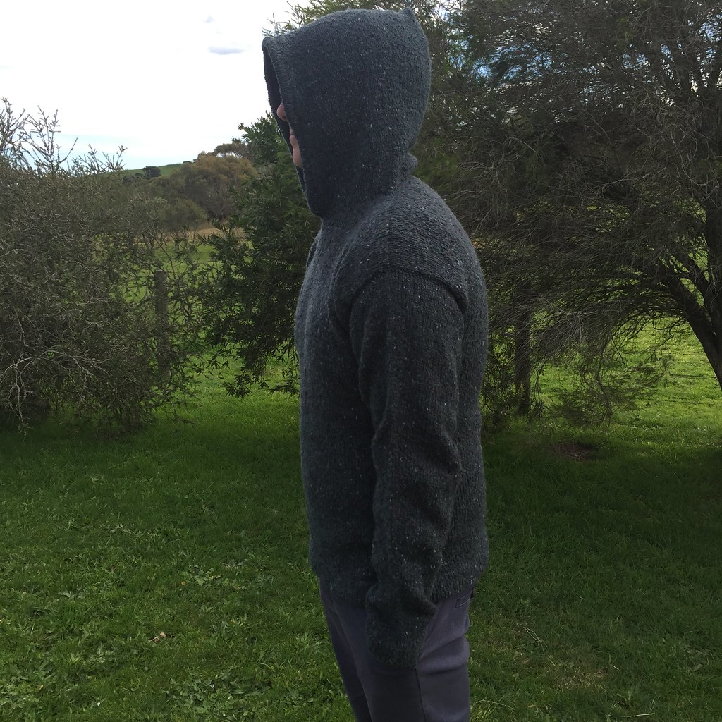 side view of matt's hoodie, knitted in jo sharp aran tweed aran in 'tartan' a dark green colour. with his hood up.