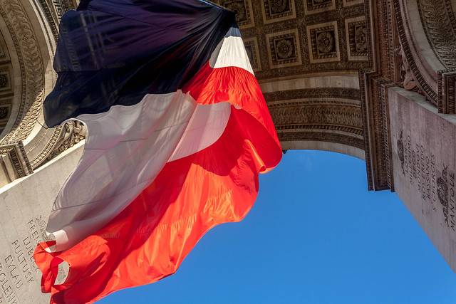 The French flag flying under Arc de Triomphe, Paris