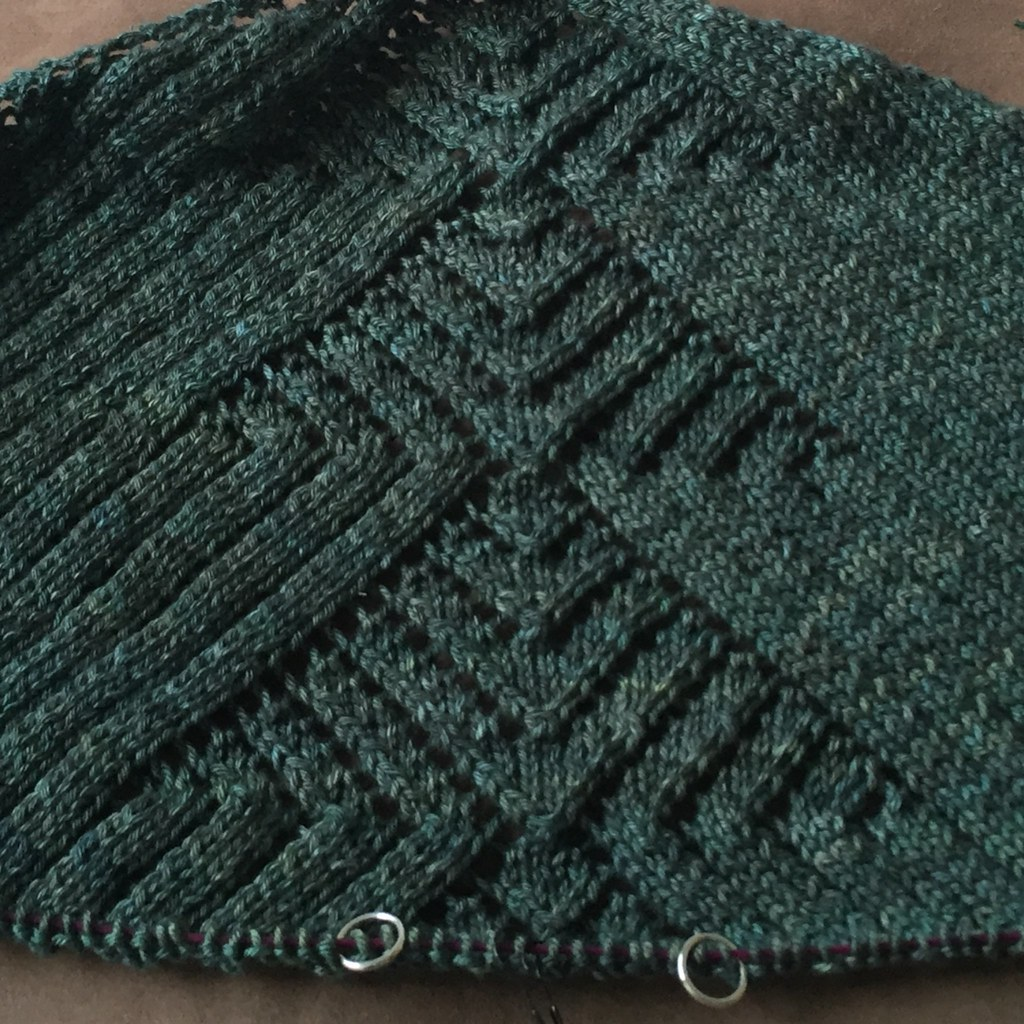 deco city shawl by amy van de laar knit in dark green 'gingko' skein merino silk sport. close up of central triangular pattern