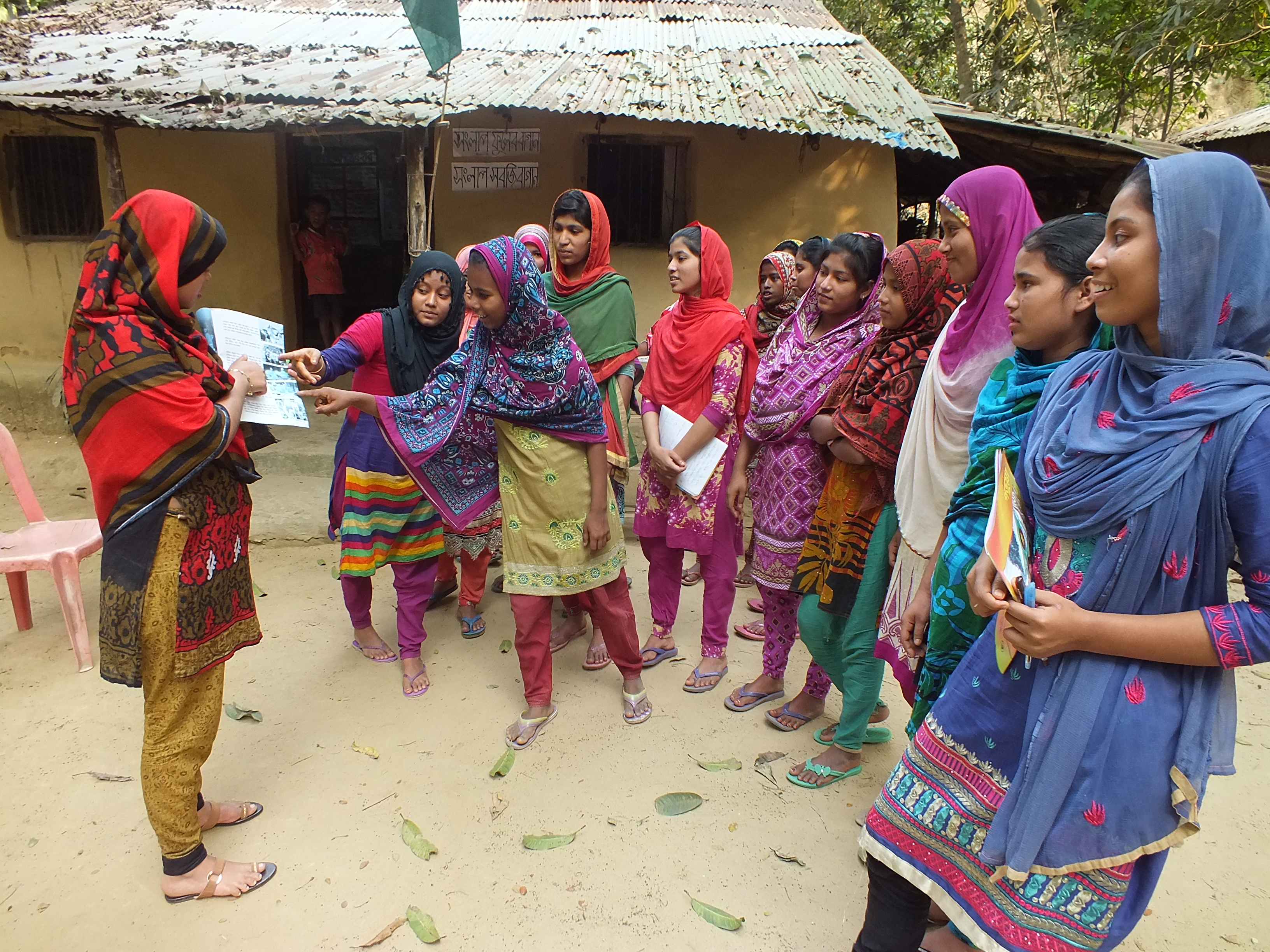 ... A group of girls attend a Shonglap session in Cox's Bazar, Bangladesh.  The peer leader (left) is discussing adolescent legal rights.