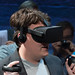Palmer Luckey (Founder, Oculus) wearing Oculus Rift consumer version and holding up Oculus Touch prototype (Half Moon) controllers (closeup headshot / bust)