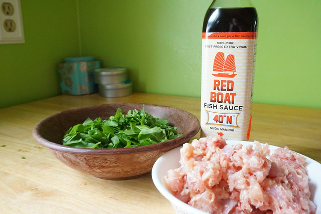 Bowls of chopped sorrel and ground chicken sit on a countertop in front of a bottle of Red Boat fish sauce (my current favorite brand)
