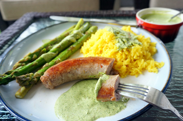 In the foreground, a pan-fried sausage, with a cut piece speared on a fork and dipped in cliantro sauce. In teh background, asparagus and rice, each with their own sauce topping.