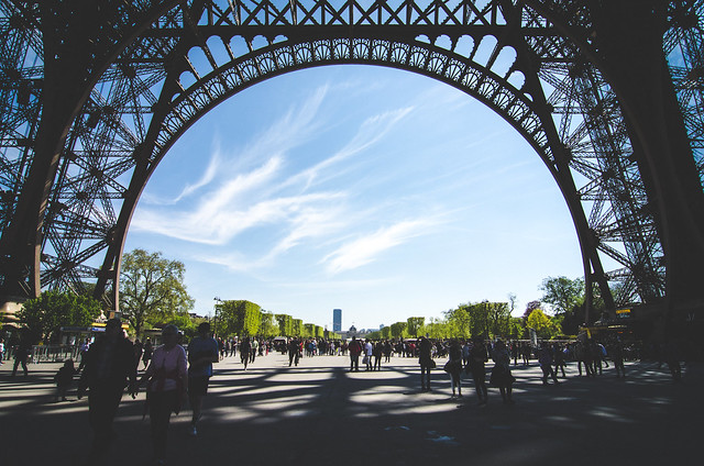 Crowds of visitors gather beneath the Eiffel Tower to marvel at the monument's strong yet delicate design.