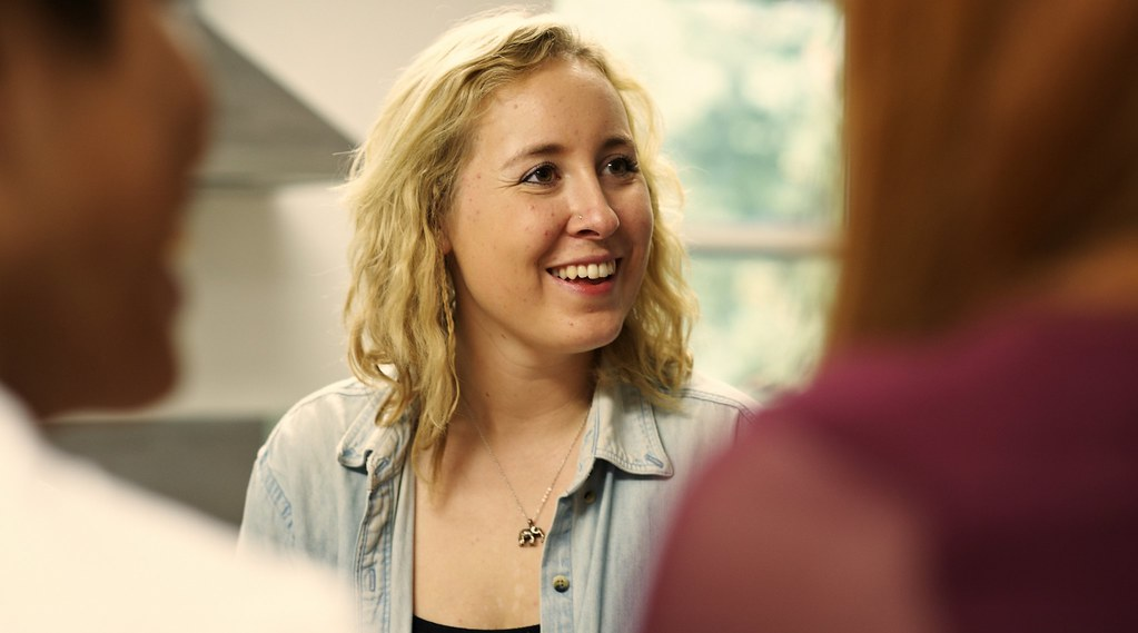 A student smiles while talking to her housemates in their kitchen