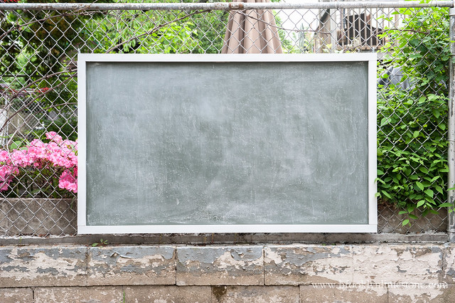 Finished Magnetic Outdoor Chalkboard trimmed in wood hanging on a wire fence