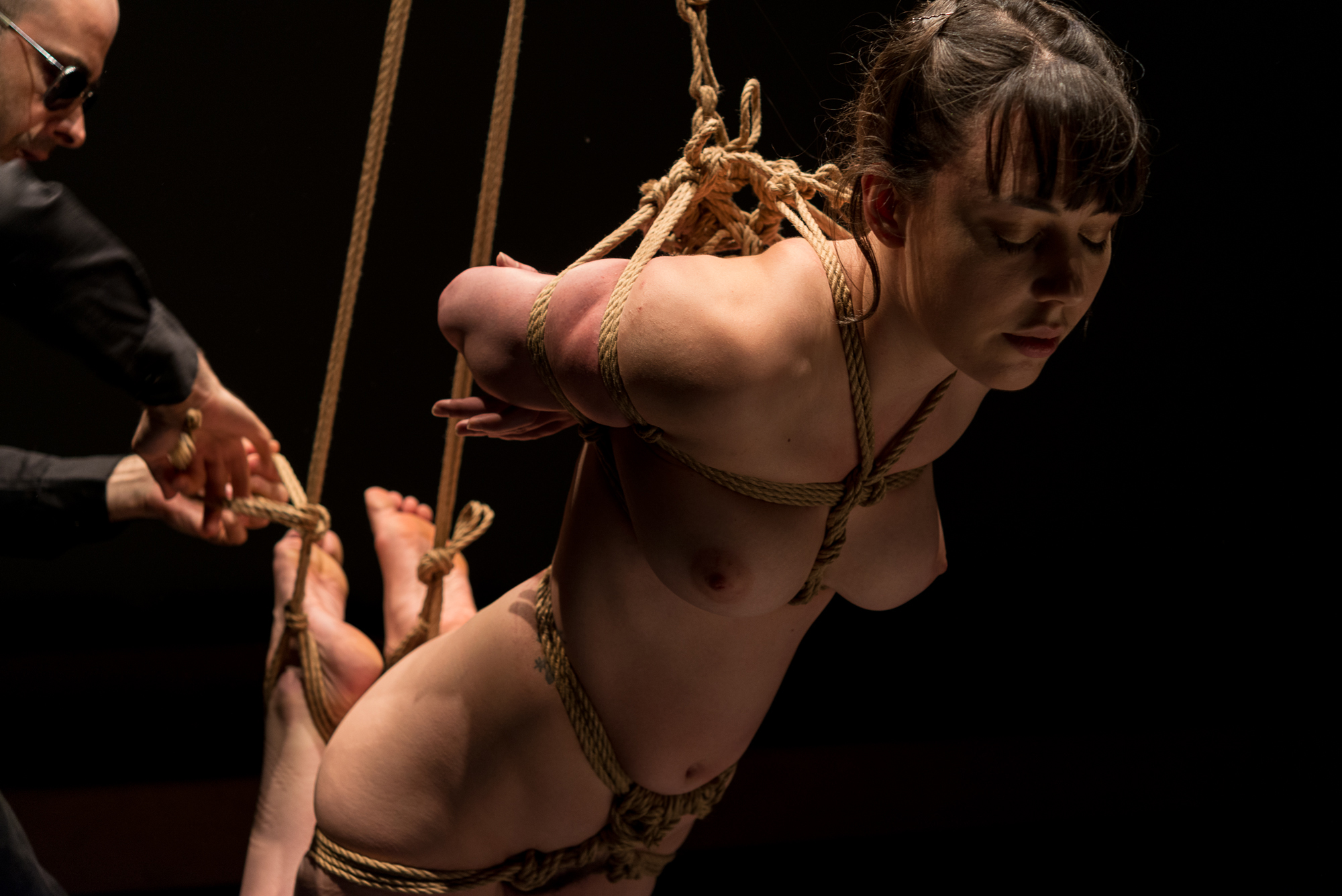 Pedro tying Gestalta in a face down suspension during a shibari performance