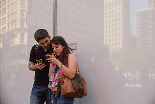 New York City Street Scenes - Couple Checking Phones in Front of White Window | by Steven Pisano