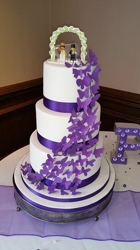 Three tiered wedding cake with a cascade of purple butterflies and a Lego bride and groom topper. | by platypus1974